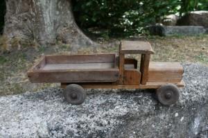Fin gammel legetøjsbil i træ med lad, ca. 33 cm lang.