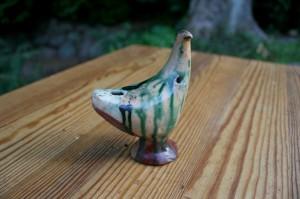Gammel piv i røv fugl i lertøj med løbeglasur, ca. 11 cm høj.