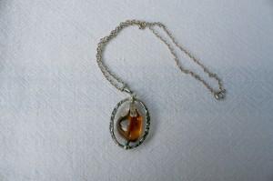 Halssmykke i sølv med rav i indfatning og sølvkæde.