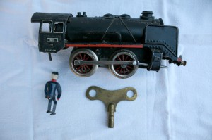 Gammelt metal legetøjstog med optræk, nøjle og lille mand føljer med, ca. 18x8x4,5 cm.
