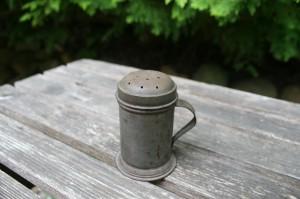 En gammel strøbøsse til salt-pebber-sukker i metal.
