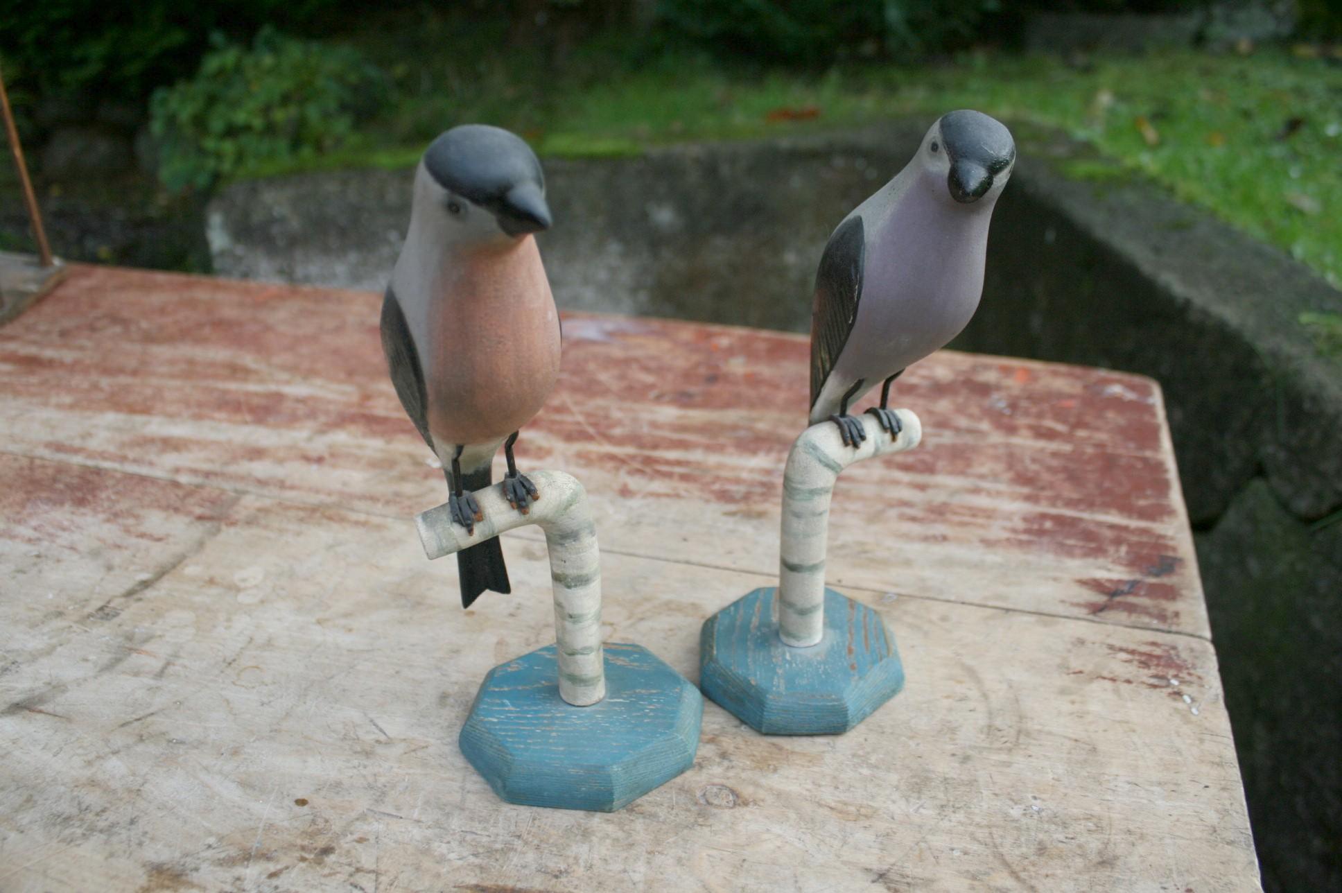 Et par udskåret fugle i bemalet træ lignende domparper.