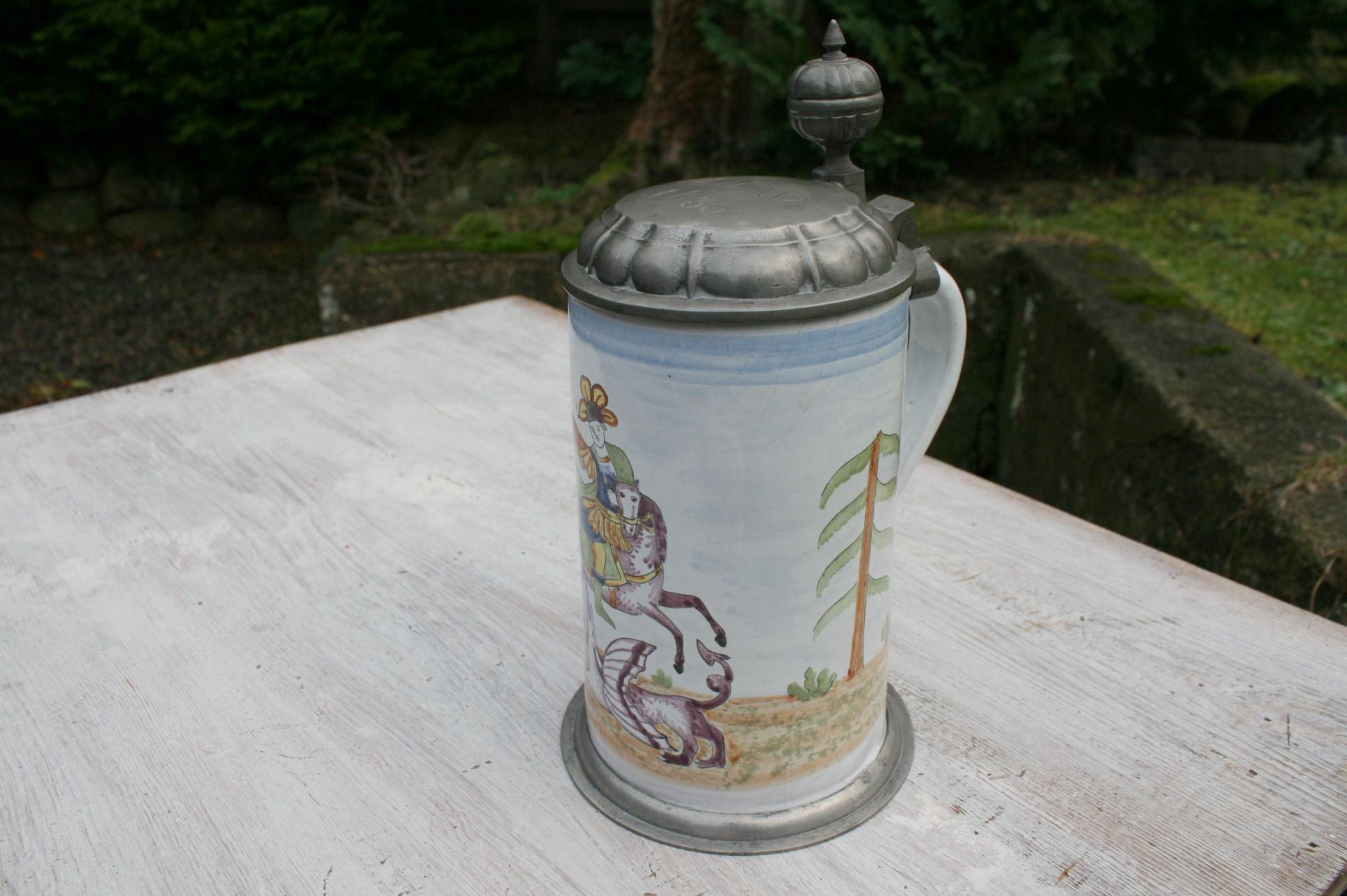 Antikt fajance krus med tin låg og dekoration af Hans Jørgen og dragen.
