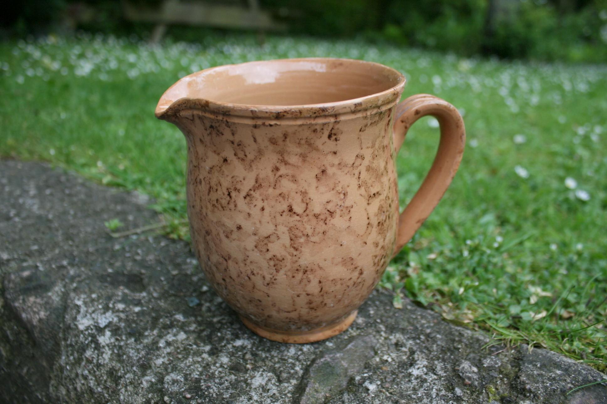 Stor flot antik mælkekande i lertøj med brungul duppe glasur.