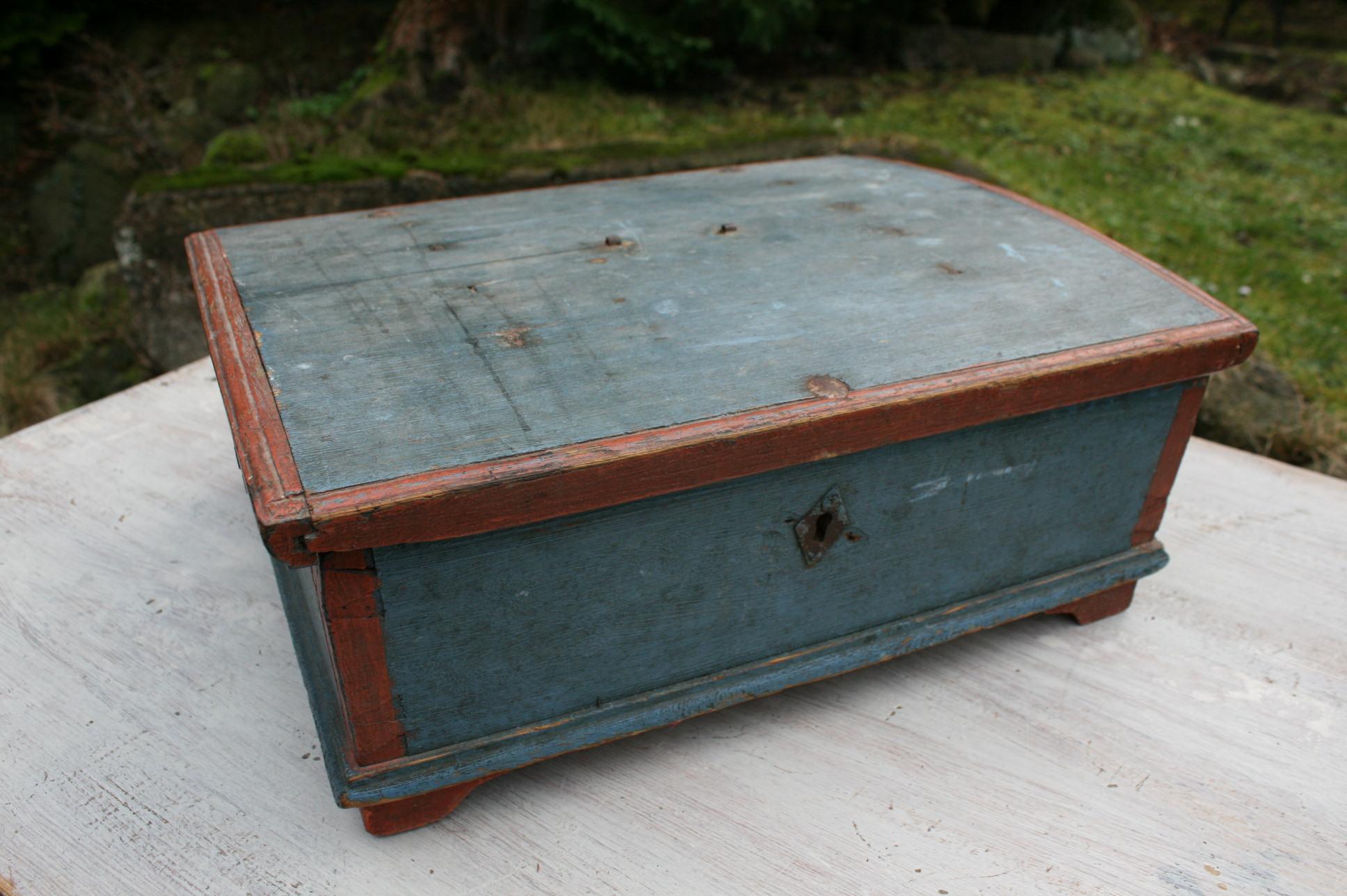 Antikt blå bemalet skrin med røde staferinger fra 1800 tallet.
