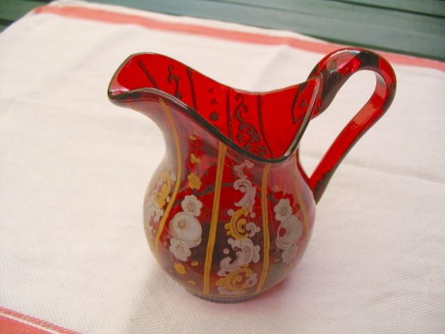 Gammel rød flødekande med påbrandt blomster dekoration.