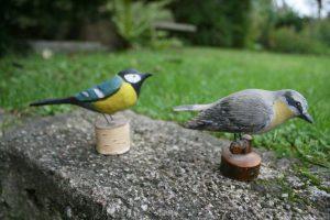 Et par gamle fugle skåret i træ på lille fod, ca. 8,5 cm høje.