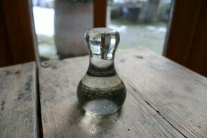En antik støder af glas til at rive farve, ca. 9 cm høj.