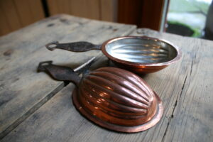 Et par små skønne kobberforme med håndtag,