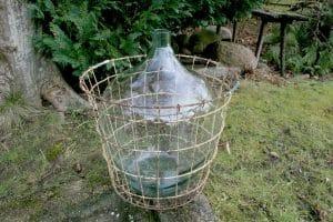 Antik glasballon / vinballon med metalkurv, ca.57 cm høj.
