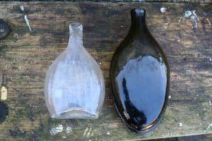 En lommeflaske/lærke klart glas og en feltflaske olivenbrun begge fra 1850-70, ca. 15 cm høj og 20,5 cm høj.