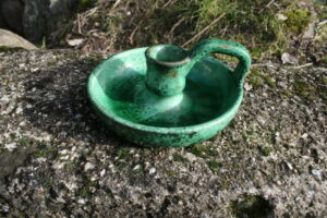 Kammerstage i lertøj grøn, ca. 13 cm i diameter og 6 cm høj.