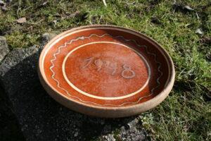 Lertøjs fad med rødbrun glasur, ca. 30 cm i diameter.