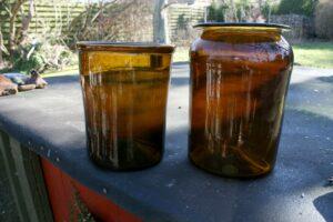 2 rav brune sylteglas fra 1800 tallets første del, ca. 18,5 cm høj og 14,5 cm i diameter, 22,5 cm høj og 16 cm i diameter.