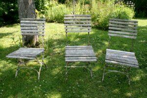 Antikke havestole med trælameller og jernstel.